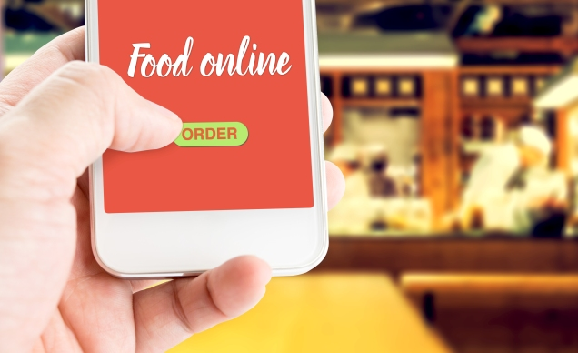 Hand holding mobile with Order food online with blur restaurant